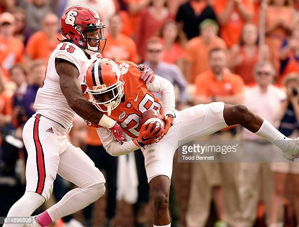Cornerback Marcus Edmond of the Clemson Tigers intercepts a pass intended for wide receiver Bra' Lon Cherry of the North Carolina State Wolfpack...