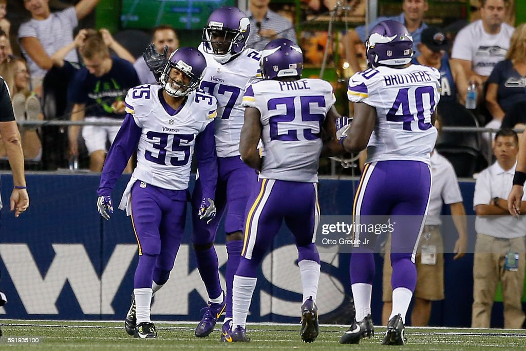 Cornerback Marcus Sherels of the Minnesota Vikings is congratulated by teammates after returning an interception for a touchdown against the Seattle...
