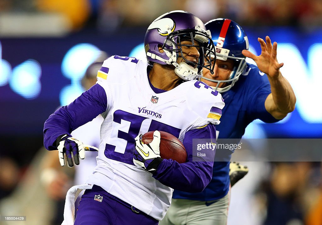 Cornerback Marcus Sherels #35 of the Minnesota Vikings returns a punt for a touchdown in the first quarter as punter Steve Weatherford #5 of the New York Giants tries to make the tackle during a game at MetLife Stadium on October 21, 2013 in East Rutherford, New Jersey.