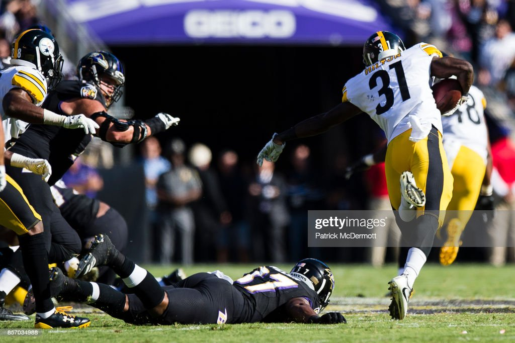 Cornerback Mike Hilton #31 of the Pittsburgh Steelers avoids the tackle of running back Javorius Allen #37 of the Baltimore Ravens after intercepting a pass in the fourth quarter at M&T Bank Stadium on October 1, 2017 in Baltimore, Maryland.
