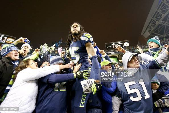 Cornerback Richard Sherman of the Seattle Seahawks celebrates with fans after the Seahawks defeat the San Francisco 49ers 2317 in the 2014 NFC...