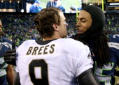 Cornerback Richard Sherman of the Seattle Seahawks hugs quarterback Drew Brees of the New Orleans Saints after the Seahawks 2315 victory during the...