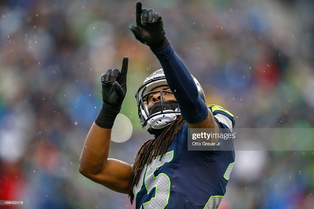 Cornerback Richard Sherman of the Seattle Seahawks points towards the stands between plays against the Oakland Raiders at CenturyLink Field on...