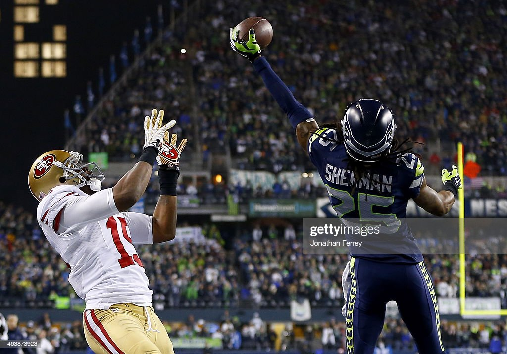 Cornerback Richard Sherman #25 of the Seattle Seahawks tips the ball up in the air as outside linebacker Malcolm Smith #53 catches it to clinch the victory for the Seahawks against the San Francisco 49ers during the 2014 NFC Championship at CenturyLink Field on January 19, 2014 in Seattle, Washington.