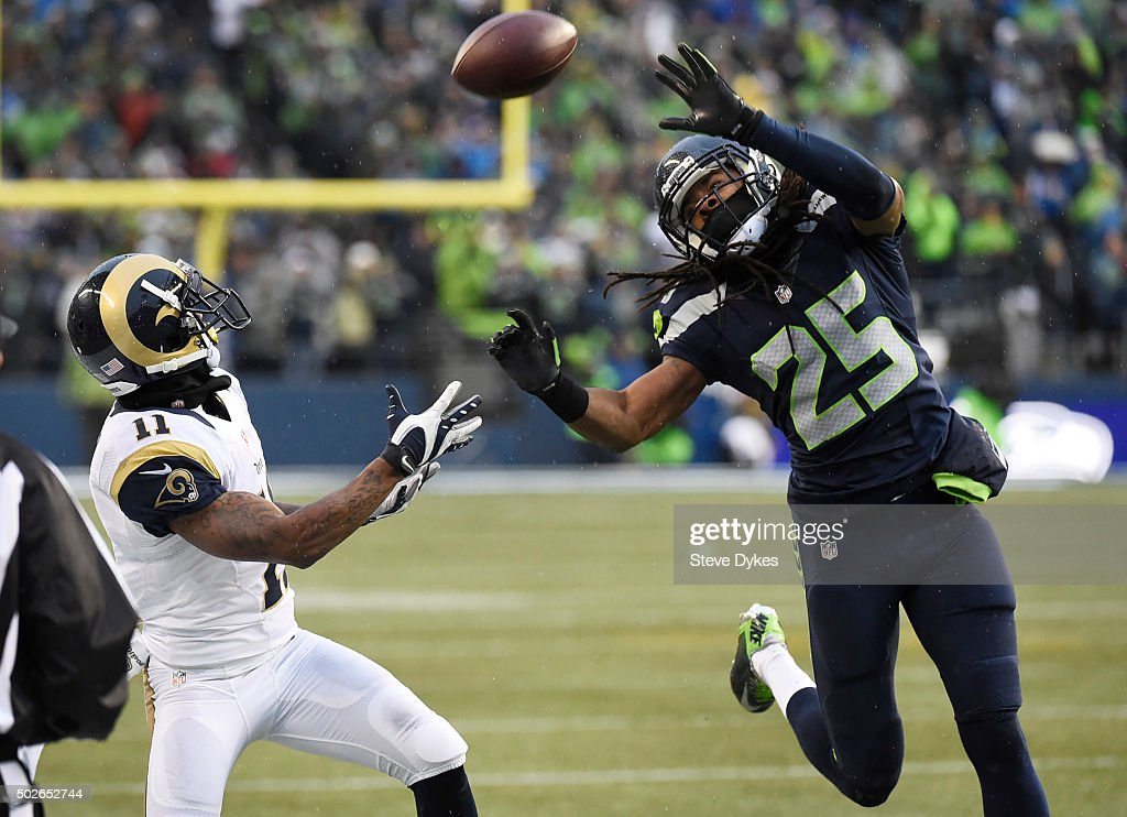 Cornerback Richard Sherman #25 of the Seattle Seahawks tries to break up a pass intended for wide receiver Tavon Austin #11 of the St. Louis Rams during the third quarter of the game at CenturyLink Field on December 27, 2015 in Seattle, Washington. The Rams won the game 23-17.