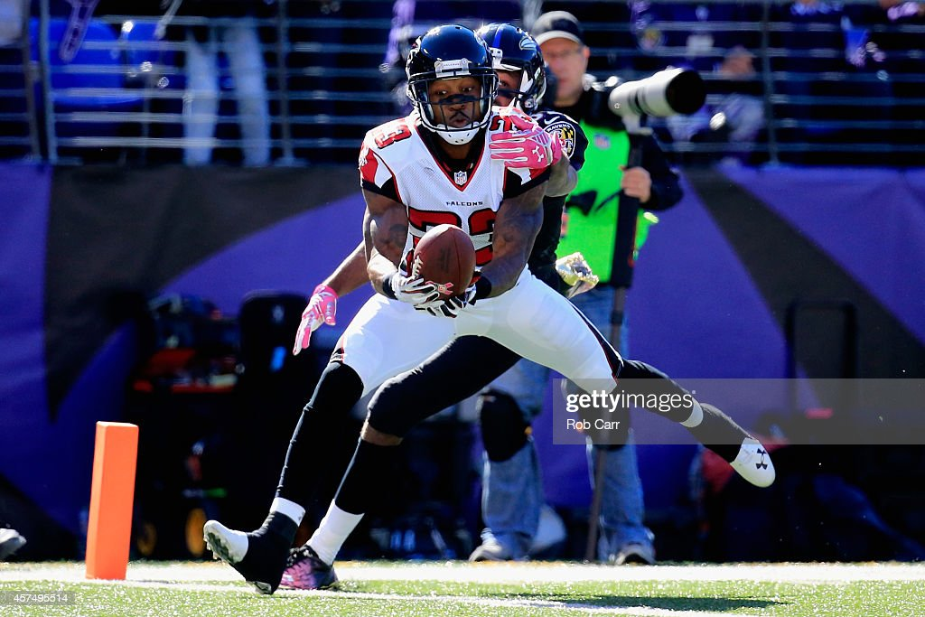 Cornerback Robert Alford of the Atlanta Falcons makes a second quarter interception while battling wide receiver Torrey Smith of the Baltimore Ravens...