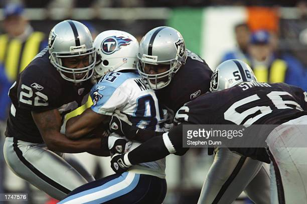 Cornerback Terrence Shaw and safety Derrick Gibson of the Oakland Raiders stop Tennessee Titans wide receiver Derrick Mason just short of a first...