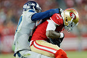 Cornerback Tharold Simon of the Seattle Seahawks tackles wide receiver Stevie Johnson of the San Francisco 49ers on an eightyard gain in the last...