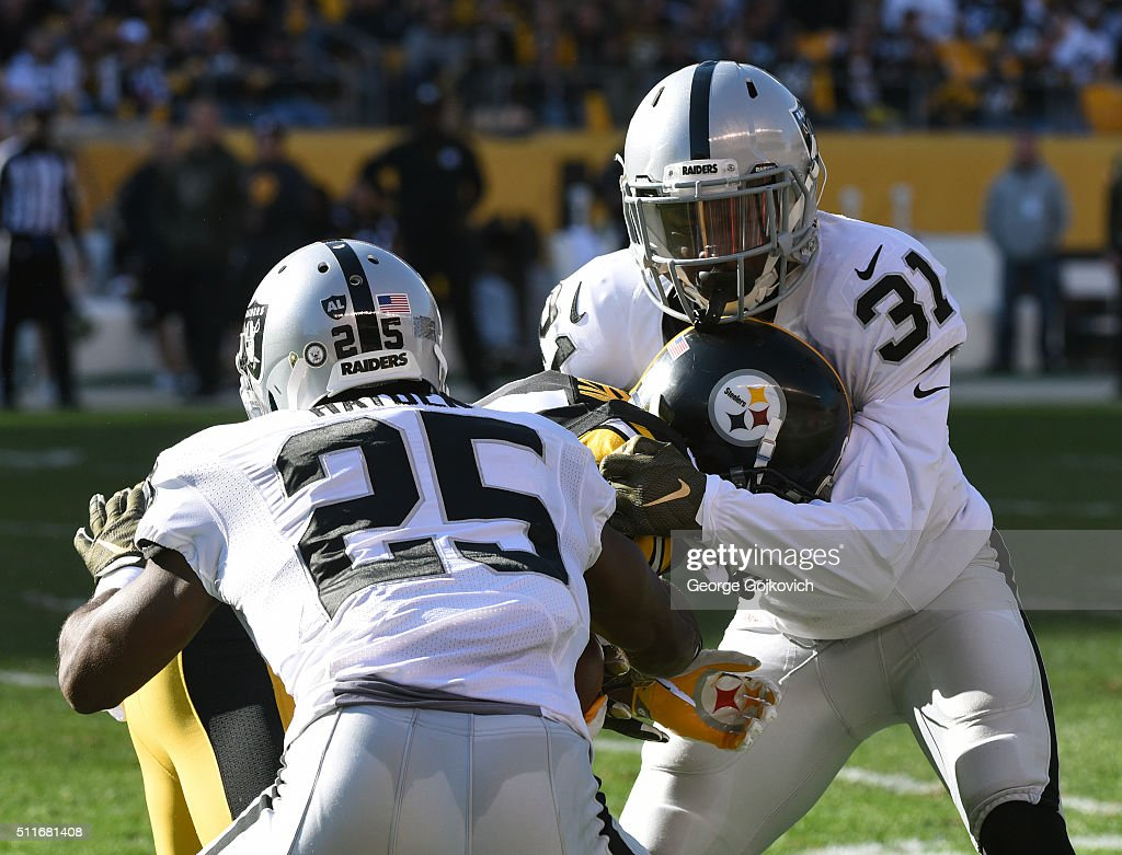 Cornerbacks Neiko Thorpe and DJ Hayden the Oakland Raiders tackle wide receiver Antonio Brown of the Pittsburgh Steelers at Heinz Field on November 8...