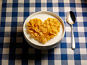 Cornflake Heart with milk in Bowl & spoon on Gingh