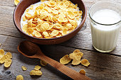 Cornflakes in a brown clay plate on a worn wooden background, next is a glass of milk and a spoon, and several flakes are scattered