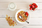 cornflakes with strawberries and milk - a healthy Breakfast on a white wooden background - top view