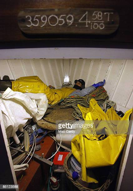 Cornish Fisherman Chris Bean's crewmate Mario 'Chino' Rios sleeps below deck as they sail a few miles out to sea near Helford on February 25 2009 in...