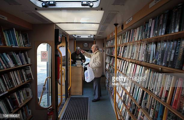 Cornwall County Council mobile library driver and assistant Andrew Reeves lends out library books to a customer from the council's mobile library...
