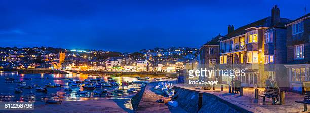 Cornwall St Ives harbour waterfront panorama warmly illuminated at dusk