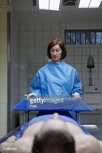 Coroner Examining Body in Morgue