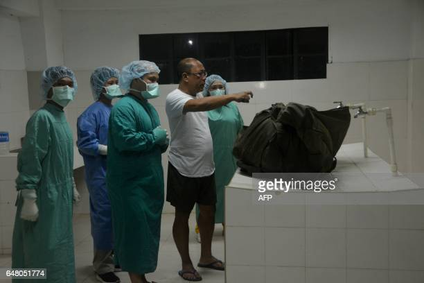 Coroners at a funeral house look at a body body containing the remains of German hostage Jurgen Kantner in Jolo Sulu province on the southern island...