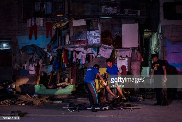 Coroners carry the dead body of Jose Arce Malozno who was shot by masked men outside their shanty house on August 18 2017 in Manila Philippines A...