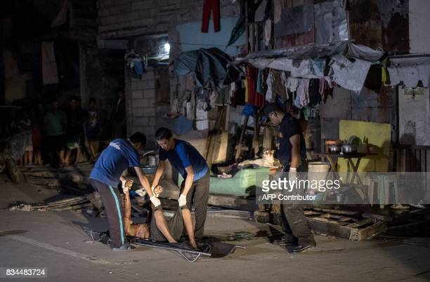 Coroners move the dead body of an alleged drug dealer killed during a police antidrug operation in Manila on August 18 2017 It's just after midnight...