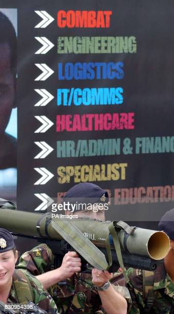 Corp Elliot Hughes holding a rocket launcher in front of the Army's slogans for its new recruitment campaign launched at Wellington Barracks London