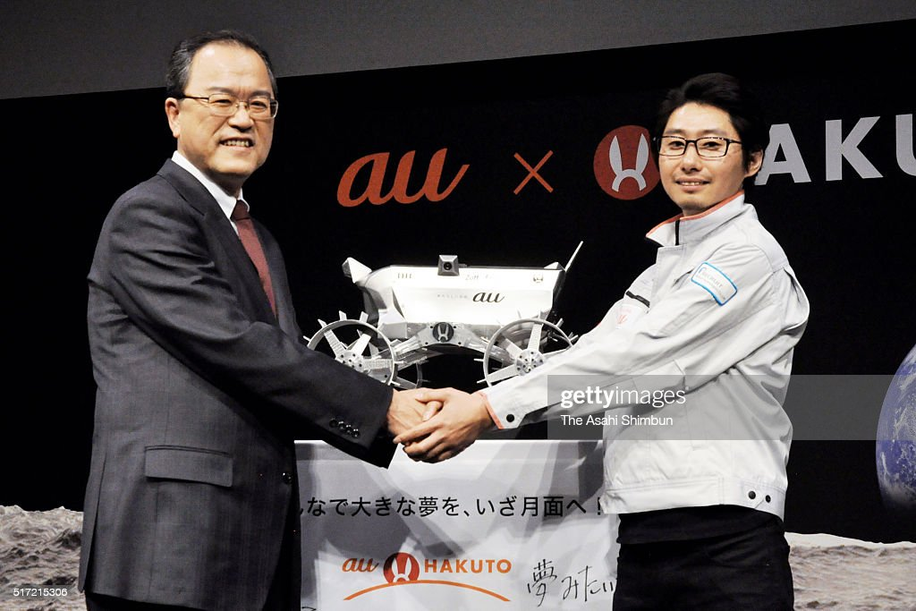 KDDI Corp President Takashi Tanaka and Hakuto team head Takeshi Hakamada shake hands during a press conference on March 23 2016 in Tokyo Japan KDDI...