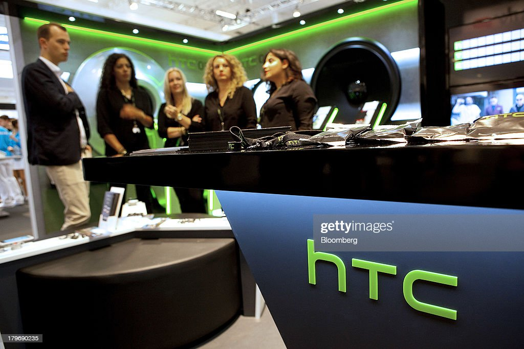 HTC Corp. representatives speak at the IFA consumer electronics show in Berlin, Germany, on Friday, Sept. 6, 2013. Global smartphone revenue will rise 22 percent in 2013, or nearly half the pace of an expected 41 percent gain in shipments, amid falling prices, according to UBS. Photographer: Krisztian Bocsi/Bloomberg via Getty Images
