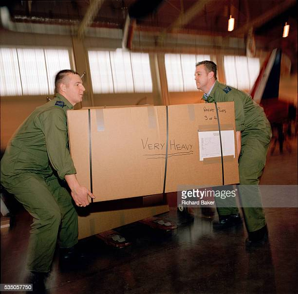 Corporal Andrew Haynes and Senior Aircraftman Michael Owen load boxes packed with the possessions and kit belonging to the elite 'Red Arrows' pilots...