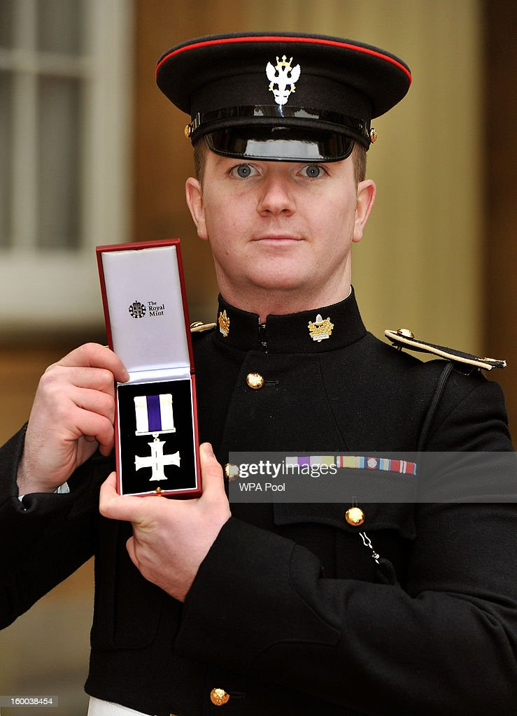 Corporal Carl Taylor of the Mercian Regiment proudly holds his Military Cross, after it was presented to him by the Prince of Wales during the Investiture ceremony at Buckingham Palace on January 25, 2013 in London, England.