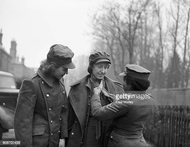 Corporal Hinds of the British Auxiliary Territorial Service shows new recruits who have just come from the clothing department how to knot their ties...