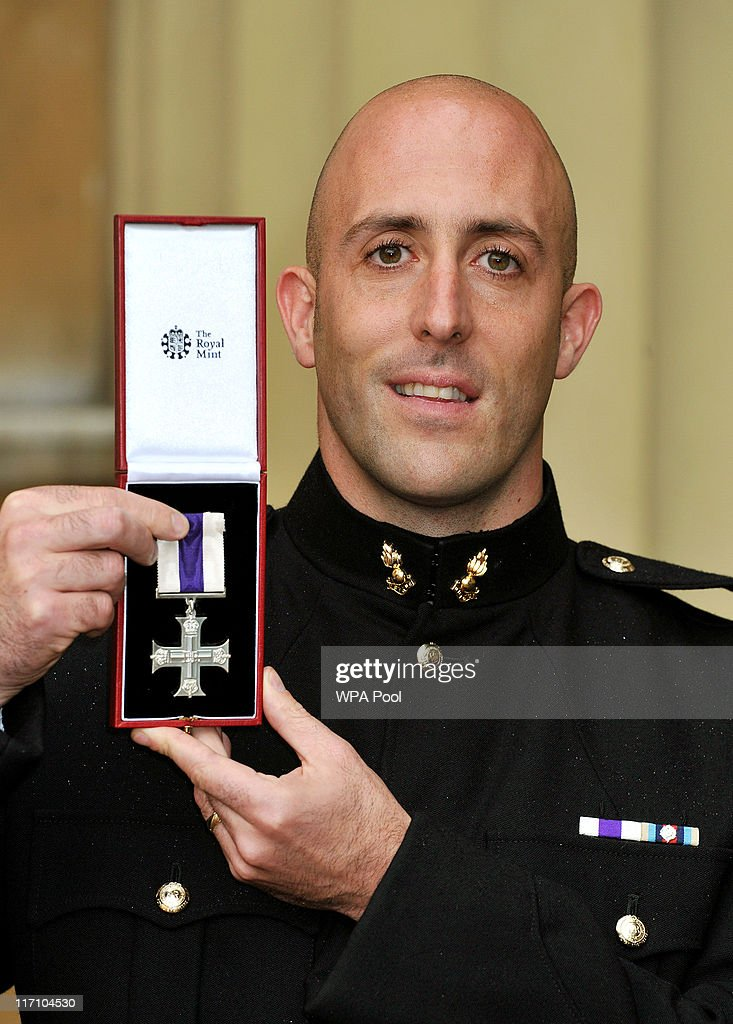 Corporal James Bedford of the Royal Engineers holds his Military Cross, after it was presented to him by the Prince of Wales, at the Investiture Ceremony on June 23, 2011 at Buckingham Palace, London.
