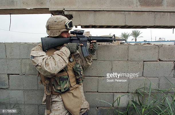 Corporal Jason Hampton from Detroit Michigan of the US Marines of the Light Armored Reconnaissance company takes up position November 12 2004 in...