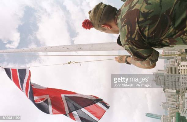 Corporal Paul Gibbons lowers the Union flag at the Nam Hang observation post over the river border crossing between the new territories of Hong Kong...