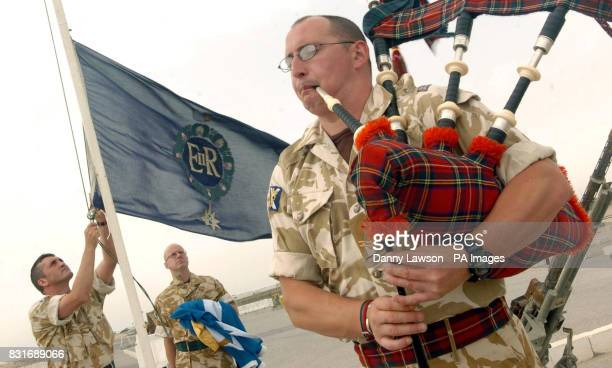 Corporal William Taylor of the former Royal Scots regiment plays the bagpipes as the old regiment's flag is lowered for the last time during a...