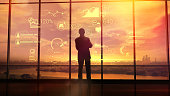 Silhouette of a man in a huge office in front of large windows viewing corporate infographics.
