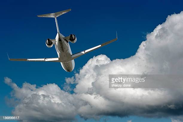 corporate jet airplane flying in cloudy sky