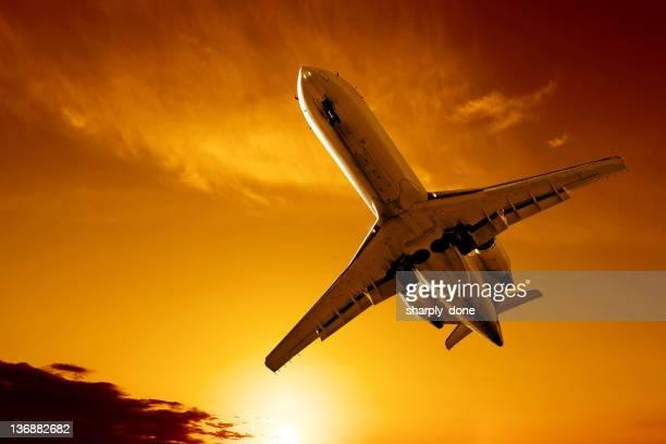 Avion jet d'atterrissage au coucher du soleil