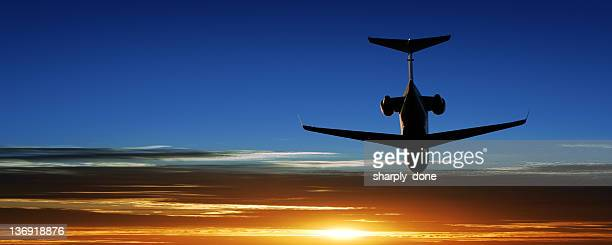 corporate jet airplane taking off at sunset