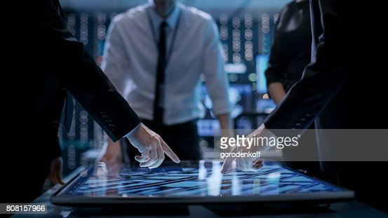 Corporate Managers Working at the Table in Monitoring Room. Room is Full of State of the Art Technology. Computers with Animated Screens. : Stock Photo