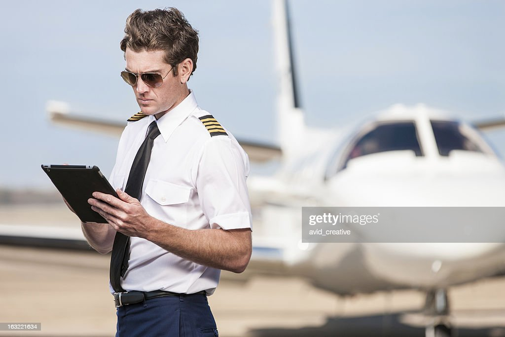Corporate Pilot Using Electronic Tablet : Stock Photo