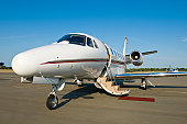 Corporate private jet at airport door open with blue sky background