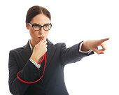 Waist up image of a business woman blowing a whistle and pointing. Concept for corporate whistle blower or industry regulator. She is dressed in formal business attire. Studio shot on a white backgrou
