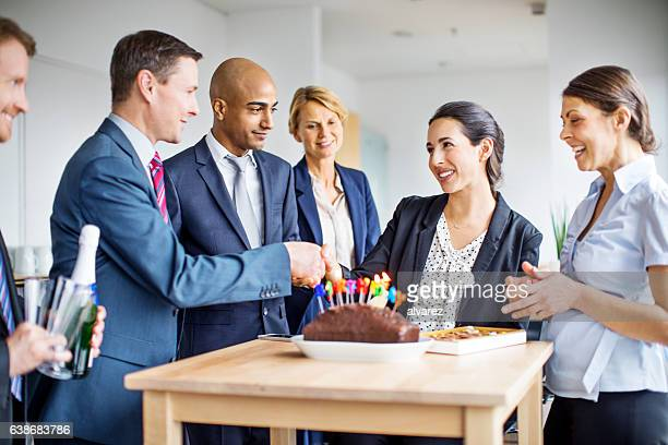Corporate workers celebrating female colleague's birthday