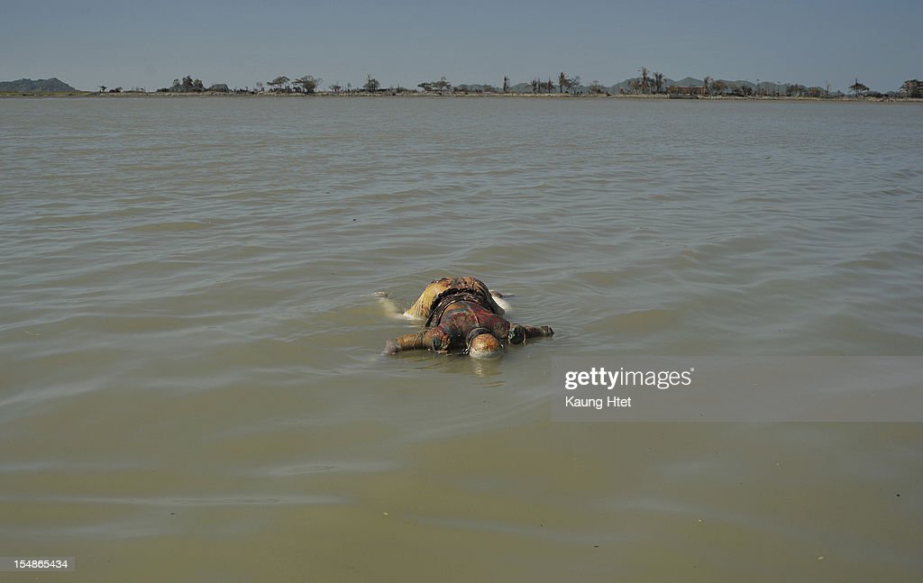 A corpse floats in river, with the burnt down Muslim Rohingya quarter No.4 in the distance, in Pauk Taw township, on October 27, 2012 in Pauk Taw, Myanmar. Over twenty thousand people have been left displaced following violent clashes which has so far claimed a reported 80 lives. Clashes between Rakhine people, who make up the majority of the state's population, and Muslims from the state of Rohingya began in June.