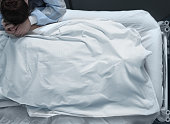 Corpse in a hospital bed covered with a head and suffering woman next to him