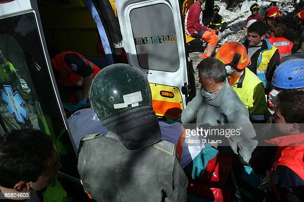 L'AQUILA ITALY APRIL 06 A corpse is placed into an ambulance by rescue workers after being found in a destroyed building on April 6 2009 in L'Aquila...