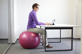 man on stability ball working with tablet - correct sitting position at workstation
