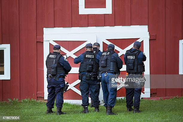 Correction officers search outbuildings on a farm as the manhunt for convicted murderers Richard Matt and David Sweat continues on June 26 2015 in...