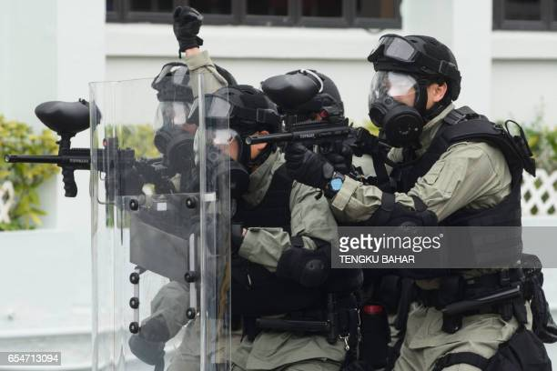 Correctional Services Department personnel clad in riot gear and nonlethal weaponry demonstrate tactics to counter a prison hostage situation during...