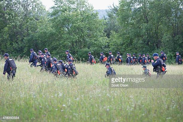 Corrections officers search a field as the manhunt for convicted murderers Richard Matt and David Sweat continues on June 24 2015 in Malone New York...