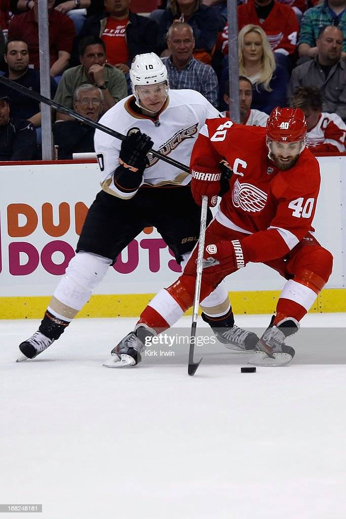 Correy Perry #10 of the Anaheim Ducks and Henrik Zetterberg #40 of the Detroit Red Wings battle for control of a loose puck during Game Three of the Western Conference Quarterfinals during the 2013 NHL Stanley Cup Playoffs on May 4, 2013 at Joe Lewis Arena in Detroit, Michigan.